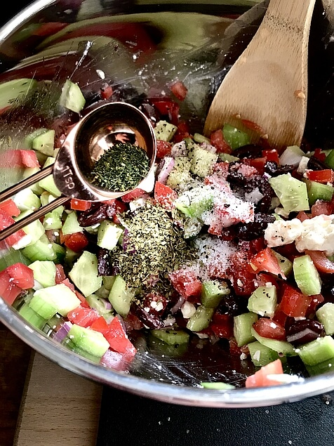 All of the fresh, delicious Greek salad ingredients being thoroughly stirred together with a wooden spoon, as the herbs and spices are added with a 1 tablespoon measuring spoon.