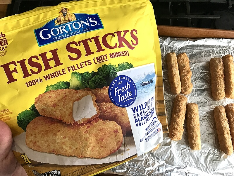 Bag of Gorton's Fish Sticks, picture and brand name displayed. Fish sticks being laid out on a sheet pan, lined with tin foil.
