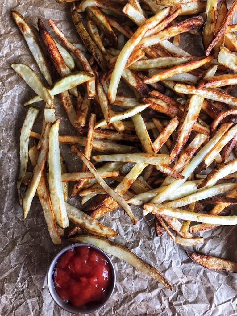 Air Fryer Crispy French Fries spread out across parchment with a small bowl of ketchup