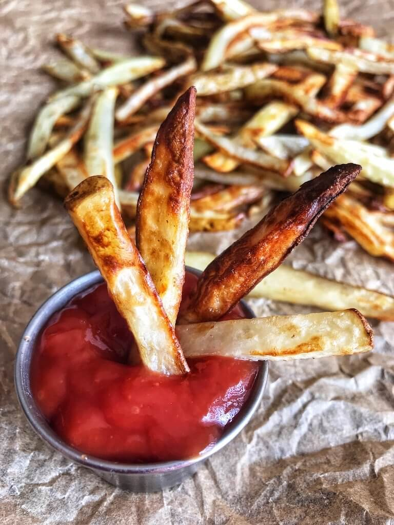 Air Fryer Crispy French Fries being dunked in ketchup