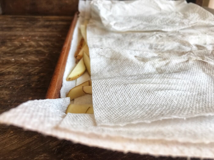 Potatoes being dried with a paper towel to make Air Fryer Crispy French Fries