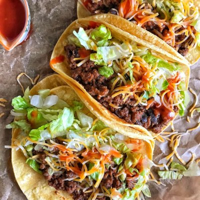 tortillas with beef and bean mixture and lettuce and cheese