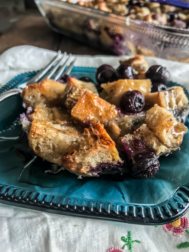 Blueberry French Toast Bake on a blue plate with a fork and a white napkin