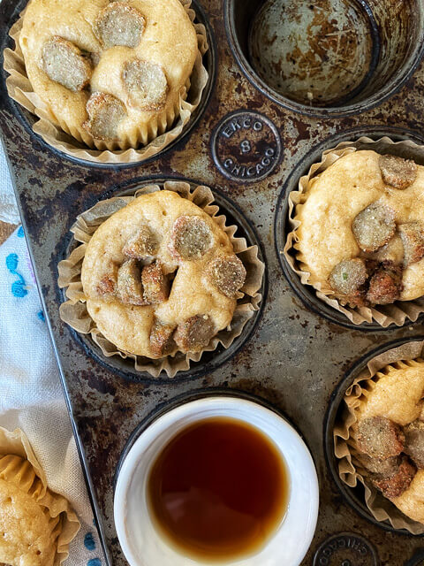 sausage pancake muffins in a muffin tin with a bowl of syrup