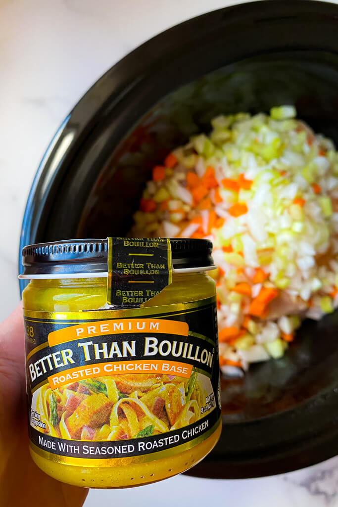 crockpot with chicken, vegetables, and container of better than bouillon