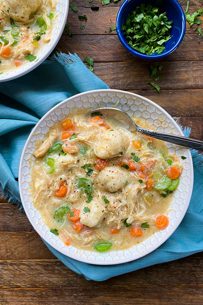 blue napkin under white bowl filled with chicken, dumplings, carrots, celery, and a silver spoon