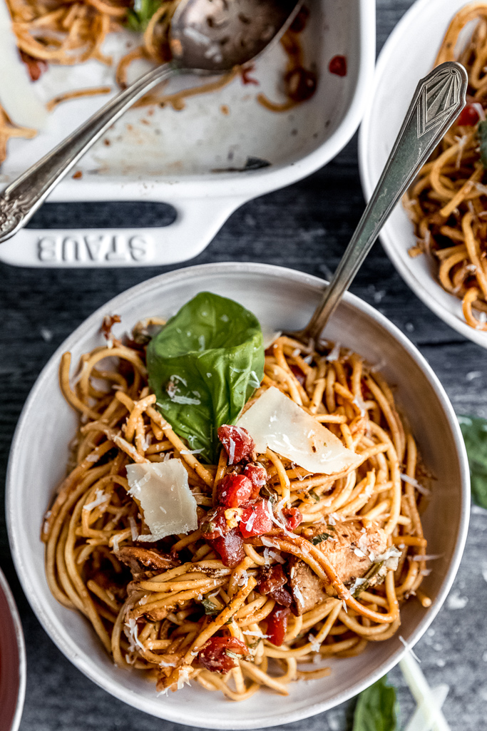 white bowl filled with bruschetta chicken spaghetti with basil and spoon