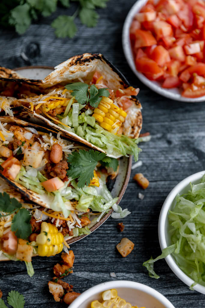 small bowls of tomatoes and lettuce with tacos loaded with lettuce corn beans and cilantro