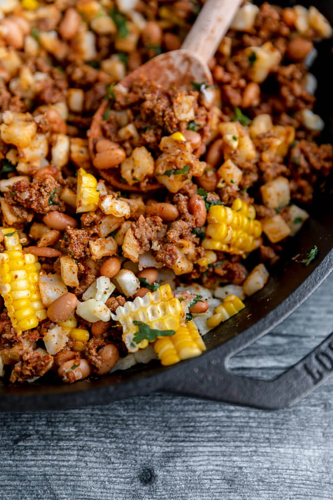 lodge skillet filled with corn, ground beef, pinto beans, cilantro, and potatoes