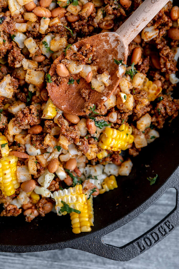 seasoned ground beef, corn, pinto beans in a big cast iron skillet for cowboy's meal