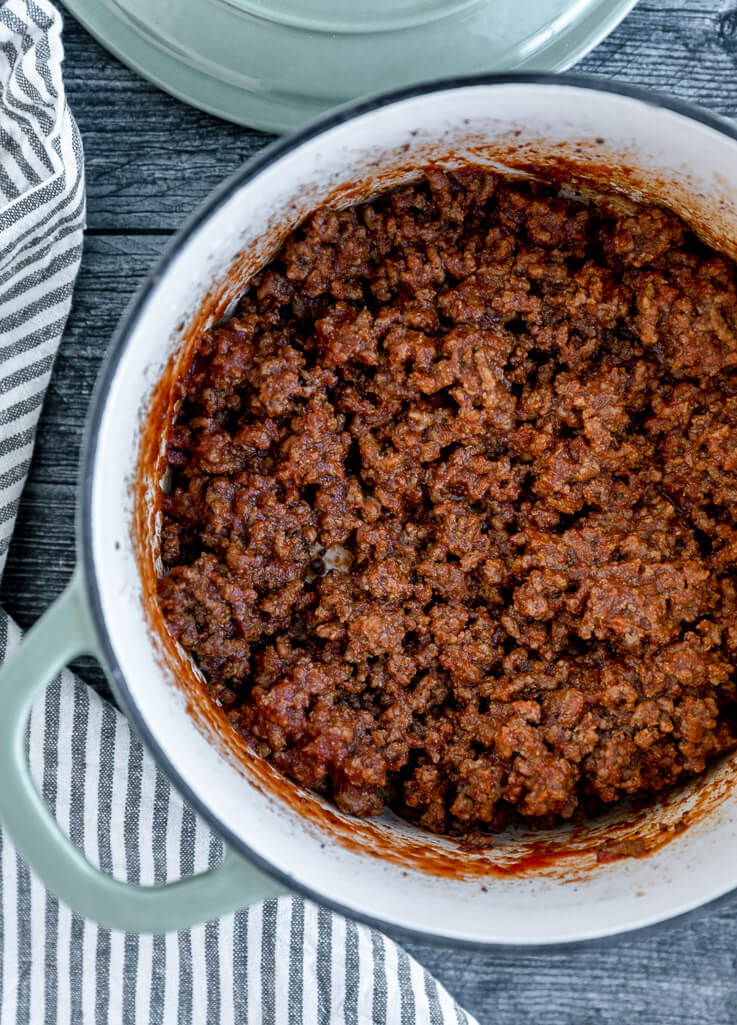 blue dutch oven with cooked seasoned ground beef