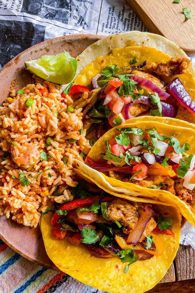 instant pot Mexican Rice on wooden plate with chicken fajita tacos topped with tomato onion and cilantro lime on the side