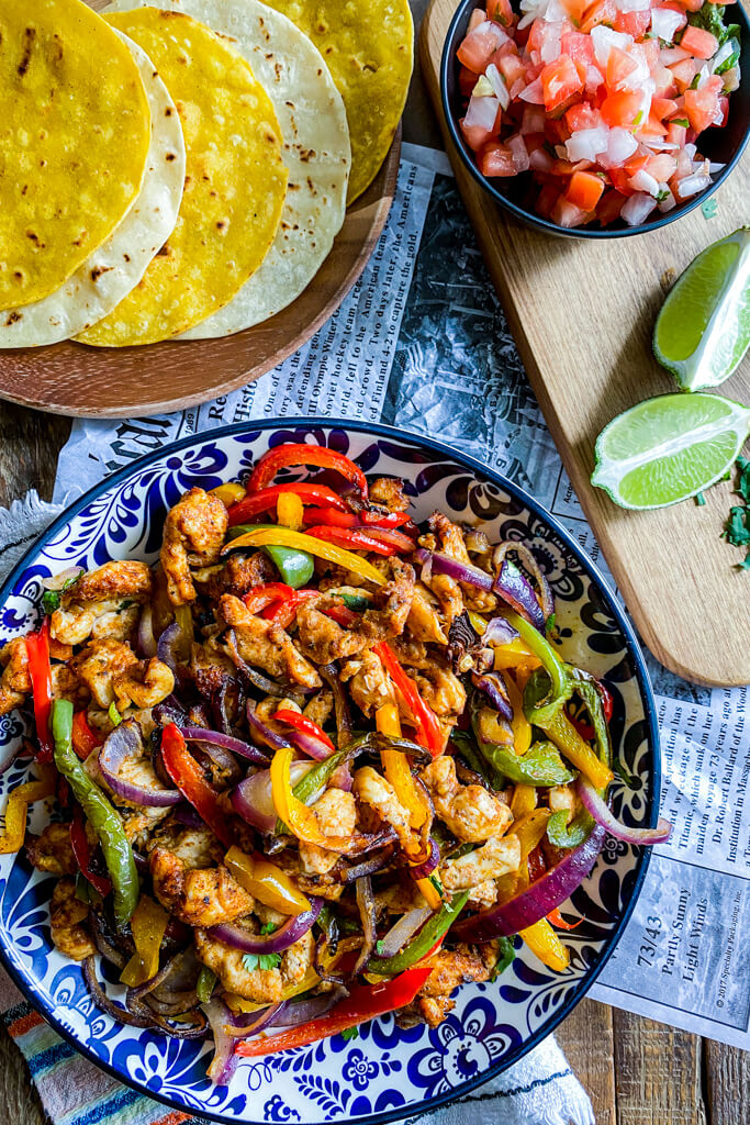 bowl of chicken fajitas with a plate of yellow and white corn tortillas, small bowl of chopped tomatoes and onions, and sliced lime