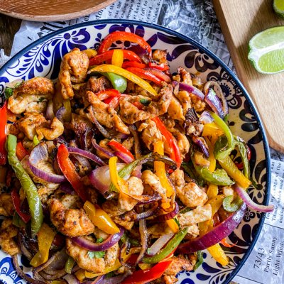 plate with fajitas chicken peppers and onion