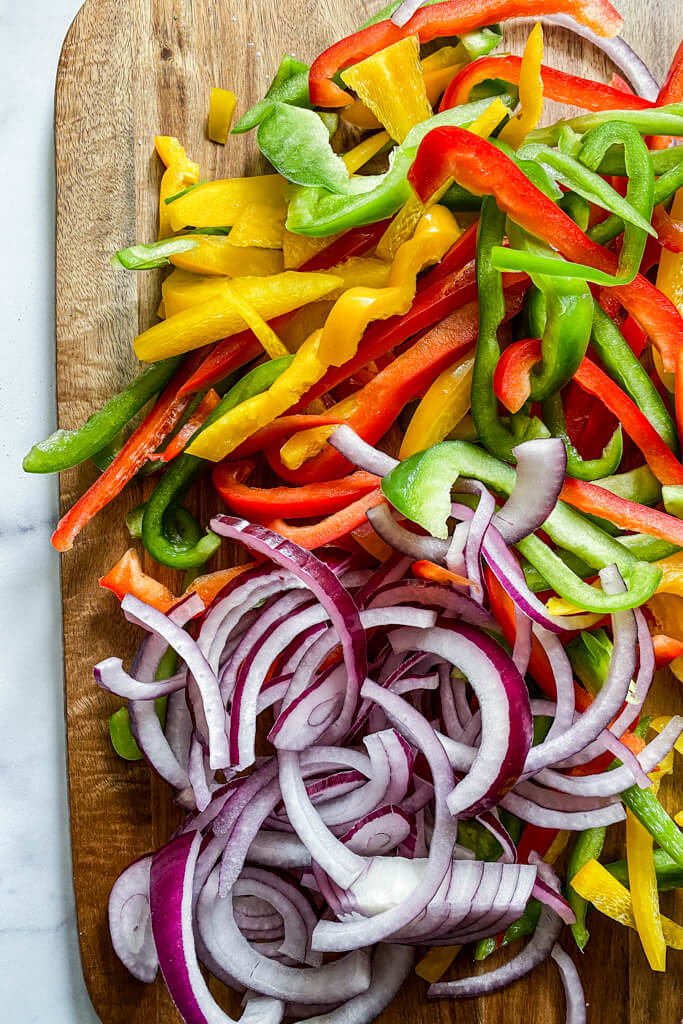 sliced red, yellow, and green peppers with red onions